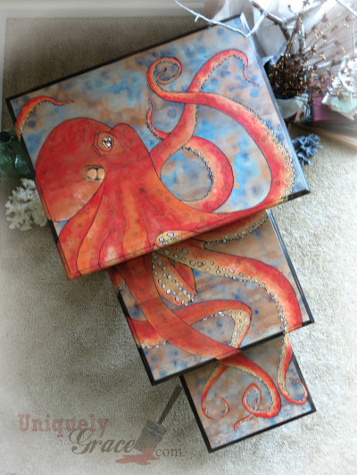 red pacific octopus hand painted onto a set of nesting tables. The blues, reds and oranges burst with color on the table top as the legs of the pieces are pure mahogany with a ebony glaze finish.