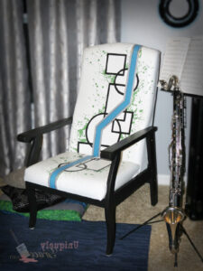 Geometric painted chair. Black with white background and splatters of greens and a blue zig zag stripe. Refinished by Uniquely Grace