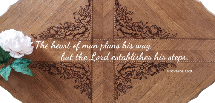 """Beautiful wood table top from birds eye view with peony flower design and the scripture Proverbs 16:9 """"The heart of man plans his way, but the Lord establishes his steps"""""""