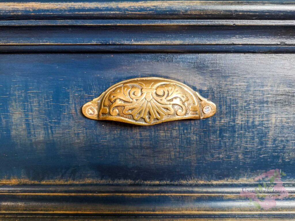 Blue rustic painted drawer with antique brass cup pull hardware. A great example for this article to help you choose Hardware.