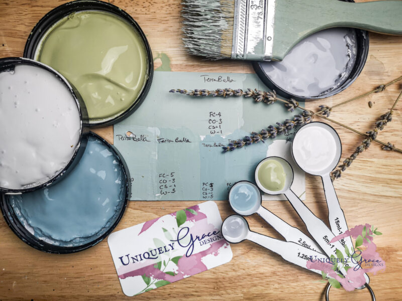 Sample of the custom mixed color light sage green with all the ingredients around the sample